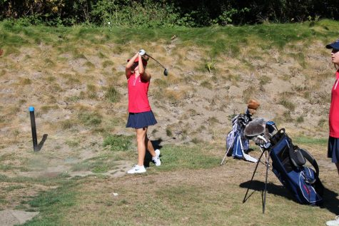 Junior Megan Stephens hits her ball out onto the green.