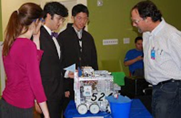 Robotics club members Katie Coates, Kourosh Arasteh, and Cary Huang show their robot at the FTC competition in Fulsom.