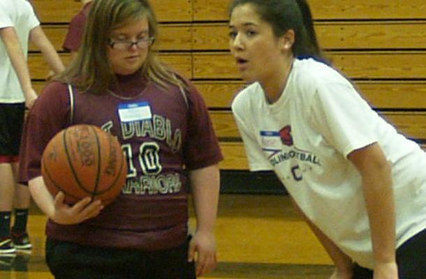 Junior Annie Doyle gives some basketball advice to one of the participants.
