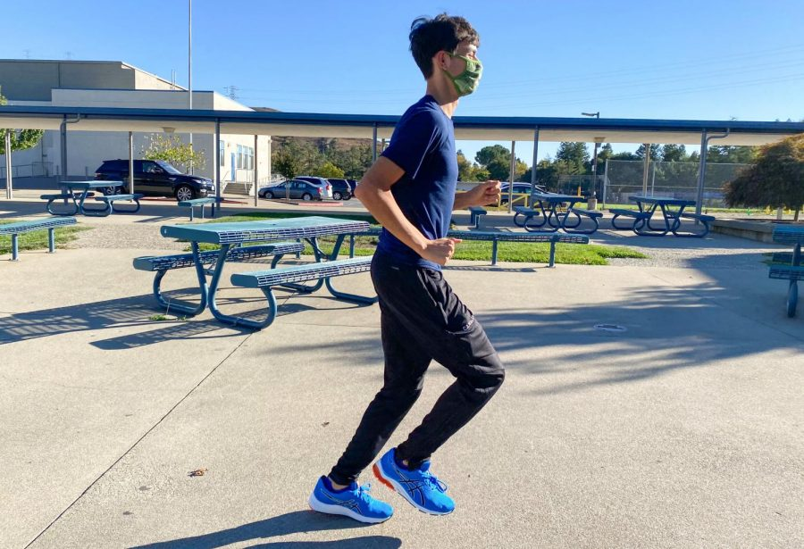 Junior Alex Canalas runs with a mask during cross country practice.