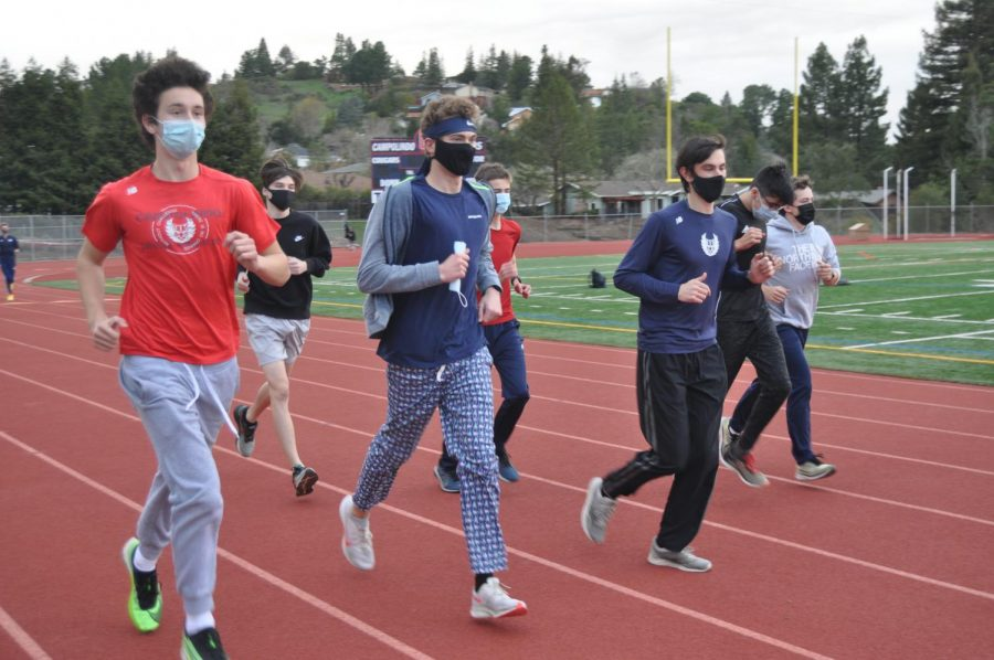 Seniors+Bradford+Martin+and+Jack+Pieper+run+with+masks+on+during+their+first+track+and+field+practice+of+the+school+year.
