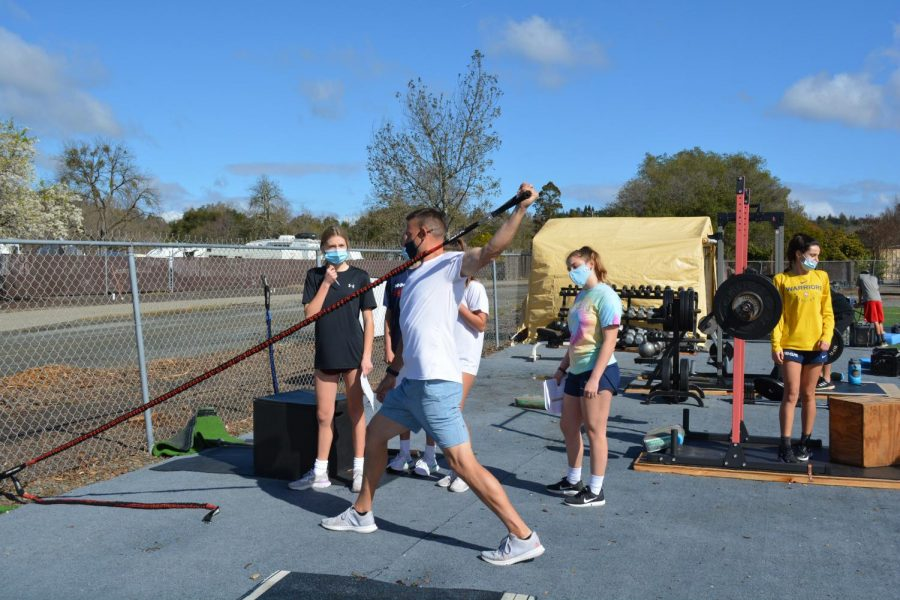 Coach Steve Hammond shows athletes how to use a resistance band at Bay Area Ballplayers.