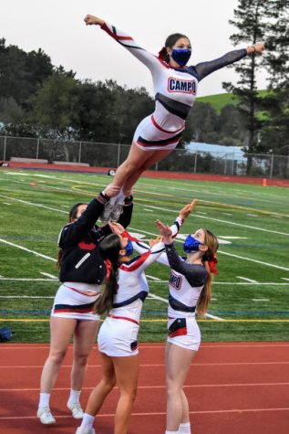 Competition cheerleaders perform a stunt at the Amador High School football game on April 3.