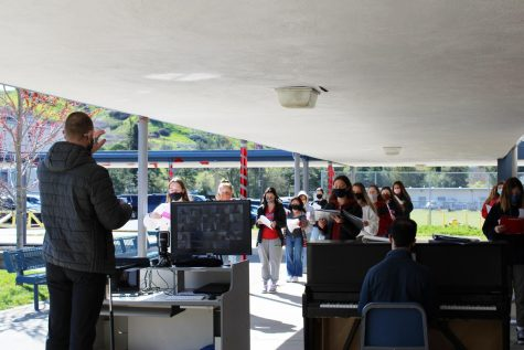 Choir teacher Mark Roberts leads the Campo choir in a socially distant, outdoor rehearsal.