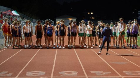 Runners from various schools line up on the track before their relay race.