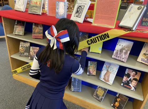 Freshman Selena Fang browses the banned books section in the library.